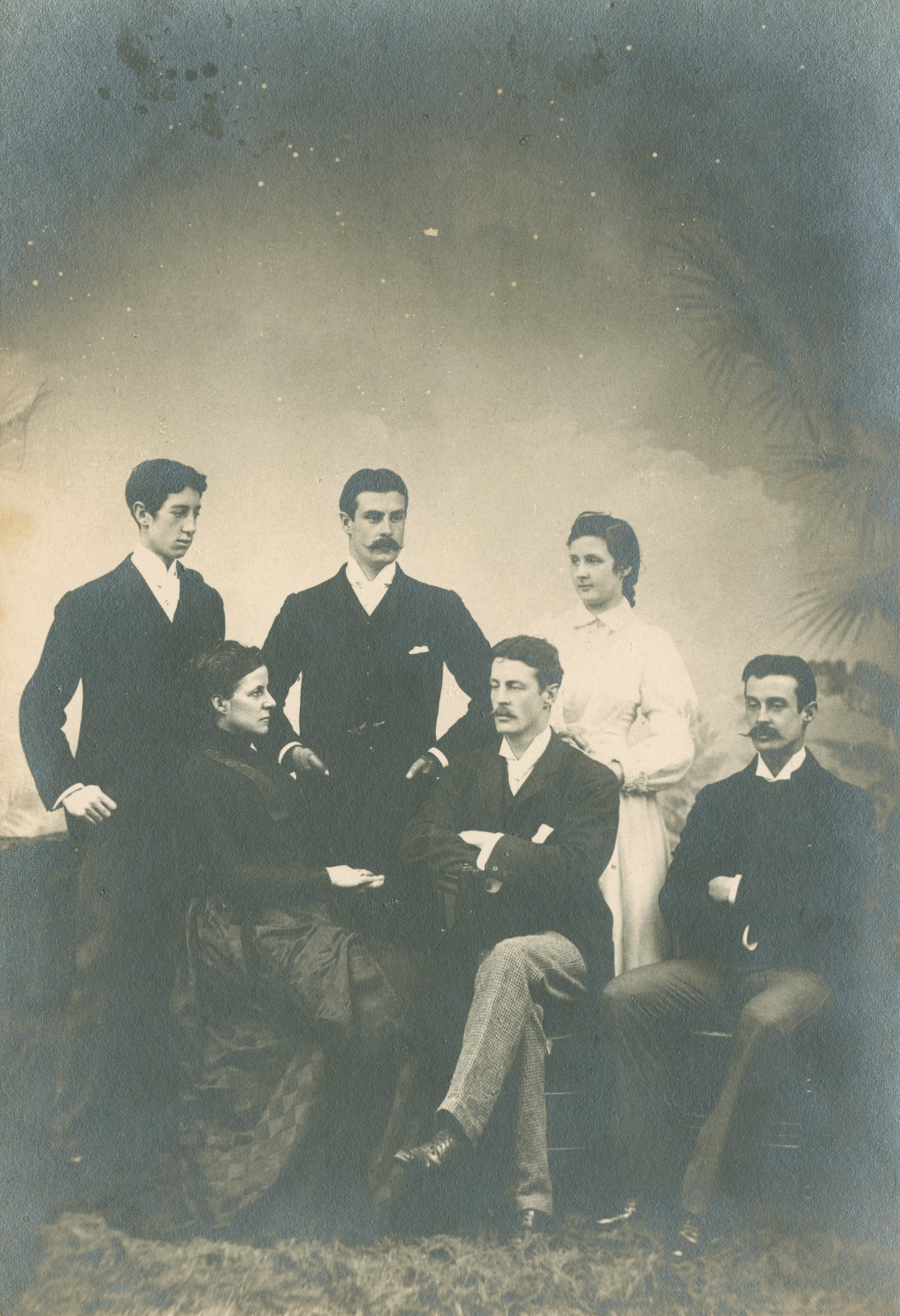 Black and white family photograph of four men and two women in period dress
