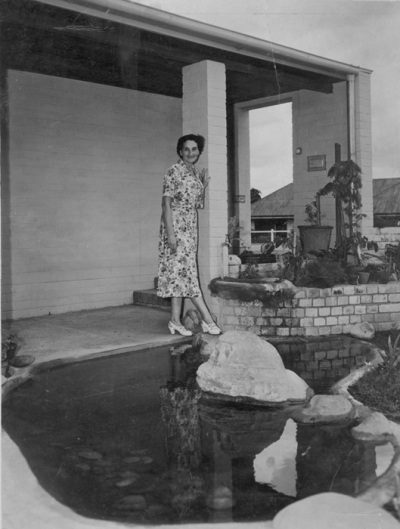 Gertrude Langer standing partially on a stepping stone in a garden pond.