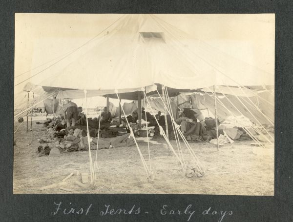 Photograph of men working in a tent captioned 'First tents - early days'