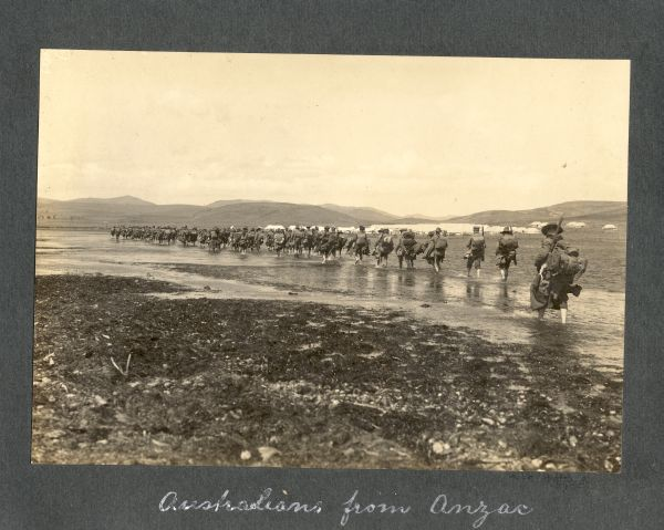 Photograph of line of soldiers marching through water captioned 'Australians from Anzac'