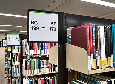 Library shelves with signage