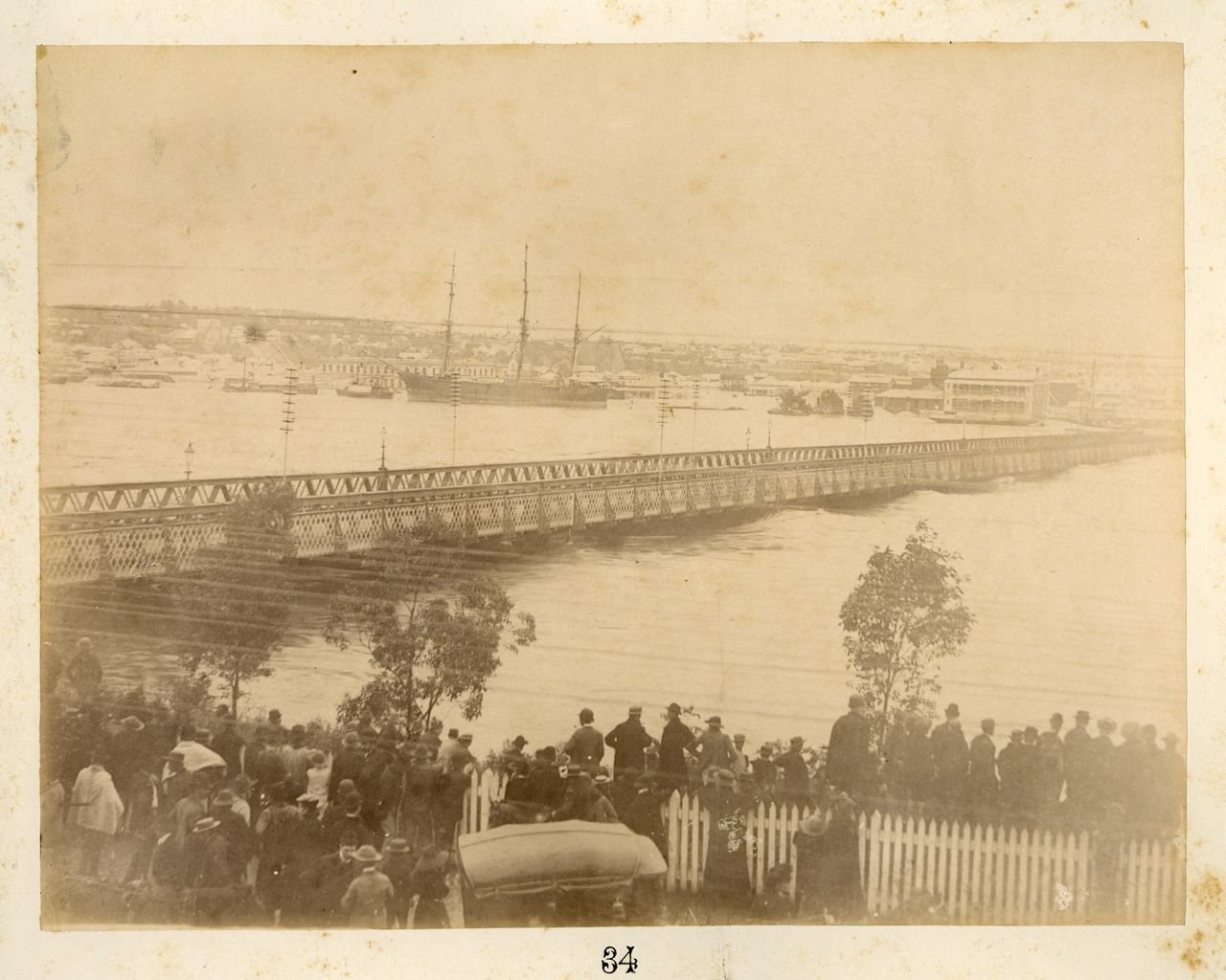 Image of people standing at North Quay looking at flooded Brisbane River and Victoria Bridge, South Brisbane in the background.
