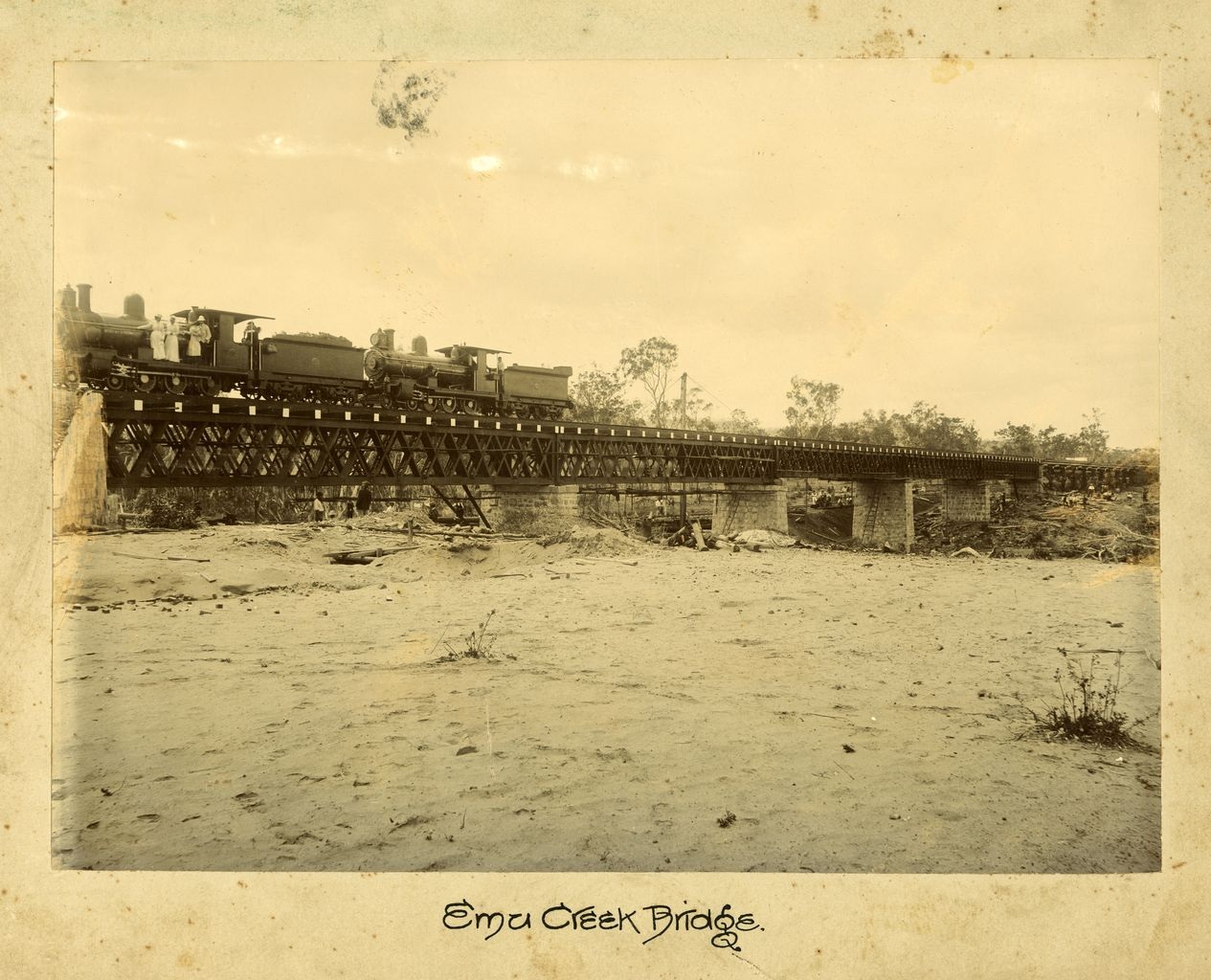 Image of Emu Creek Bridge, locomotive stopped far left of railway bridge. Three women and a man can be seen at the front of the locomotive.