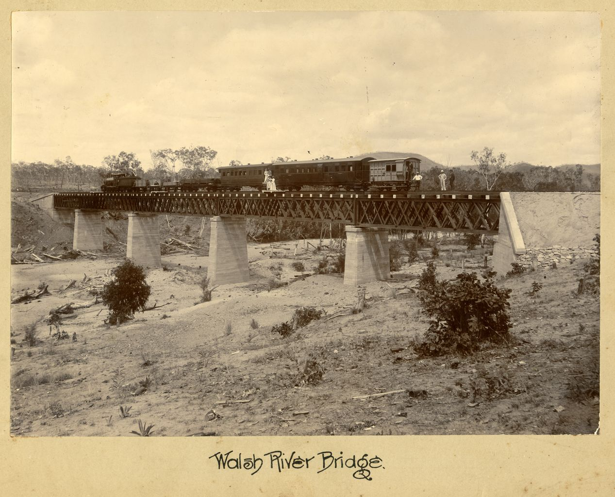 Image of Walsh River Brige, a B15 class locomotive with a mixed train stopped on railway bridge, with passengers standing on track and at entrance of carriage.